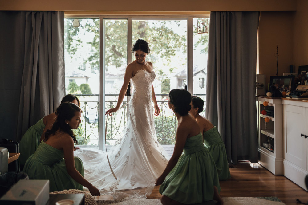 bride putting on wedding dress vancouver photography bc