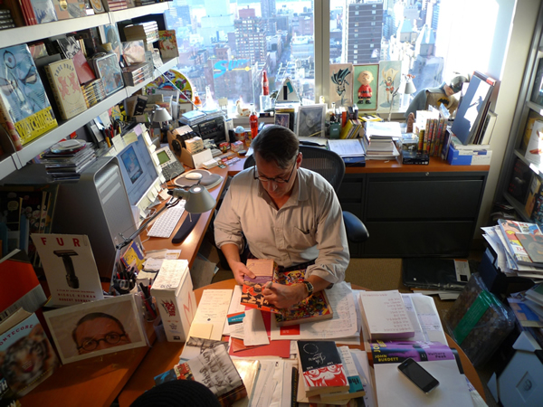 Desk of Chip Kidd, graphic designer. Look at all those book covers!