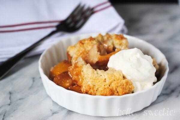 perfect peach cobbler with a dollop of whipped cream