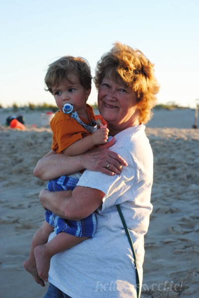 Grandma didn't mind the extra cuddles with the baby, since he was  not  digging the feel of sand.
