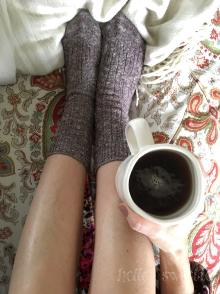 Embracing some hygge essentials: warm beverage, cozy socks & blankets, candles and baked goods!