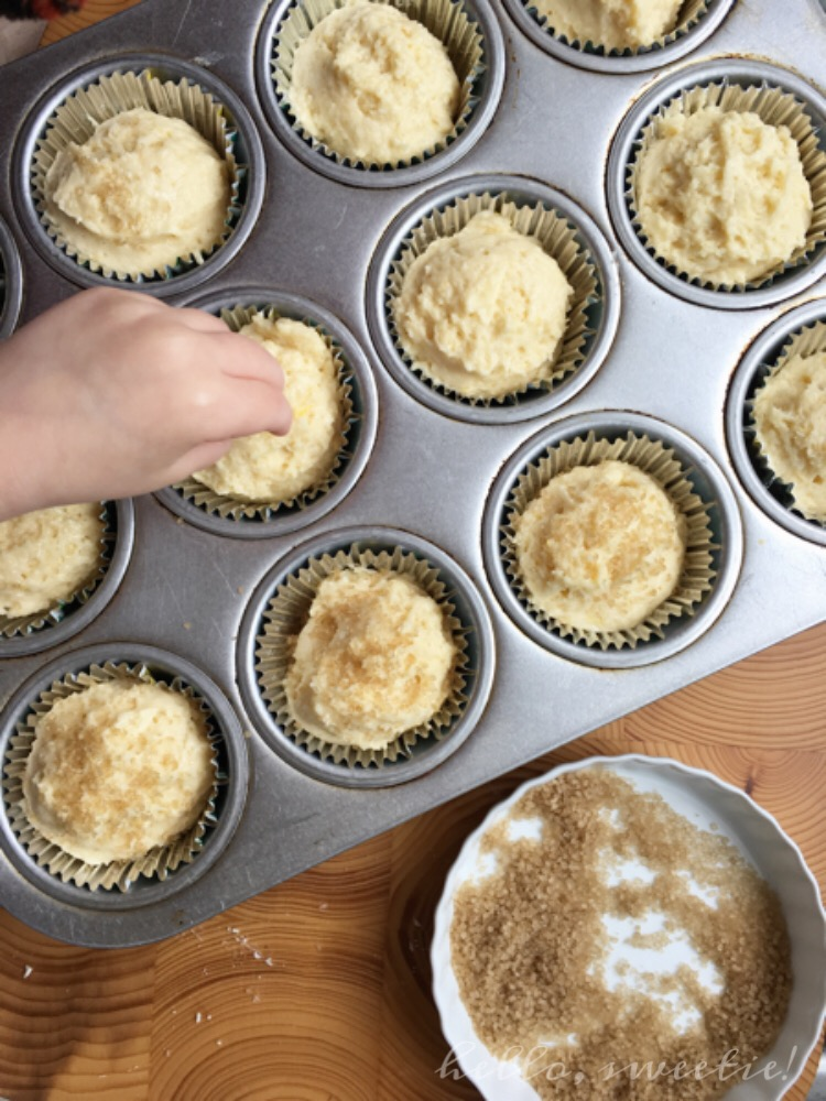 The tiny fingers of my mini chef, sprinkling a generous amount of turbinado sugar over the tops of each muffin.