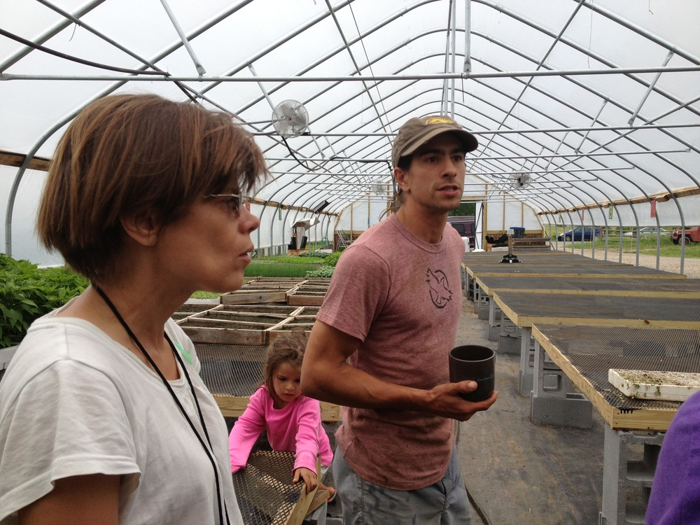 We started our tour de farms at  Fledging Crow Farm,  a CSA and market veggie operation just outside Keeseville. One of the farmers, Ian, stands in the center, showing us his propagation greenhouse.