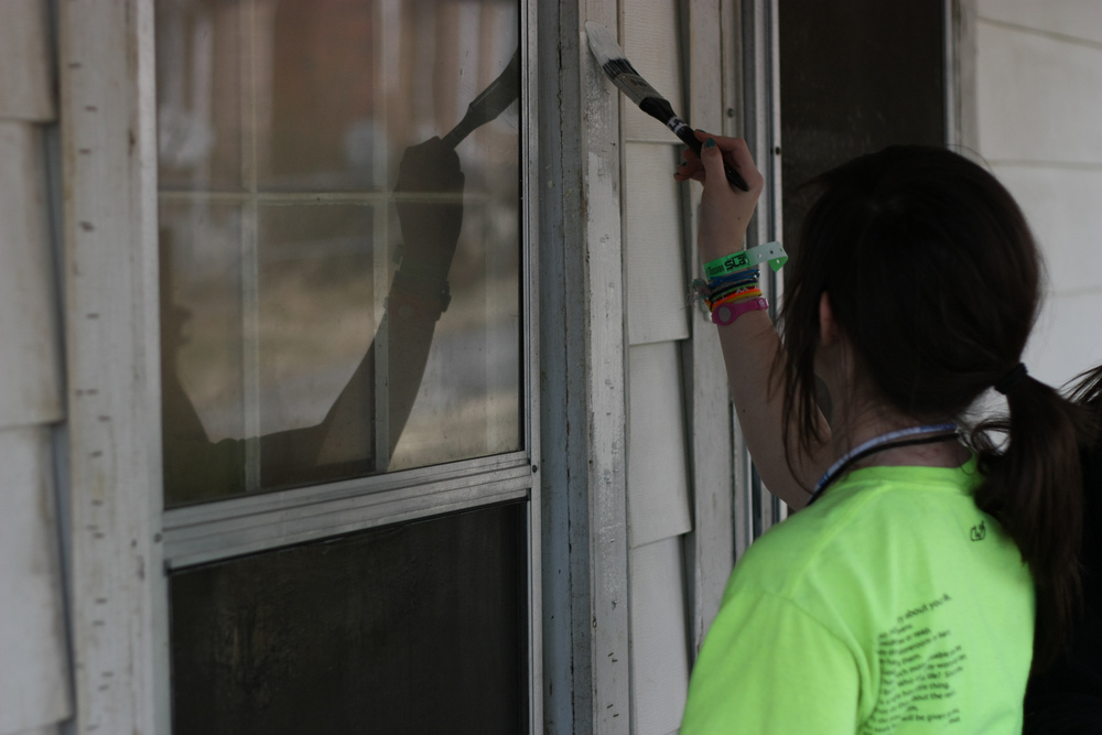 A student from Ohio volunteers with SLAM Nashville to touch up the paint on the home of an elderly widow.
