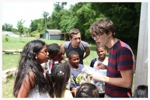Inner-city kids do often garden, but at Camp Skillz they do! Here, Summer Intern Bryan Sanders explains the process of composting to campers.