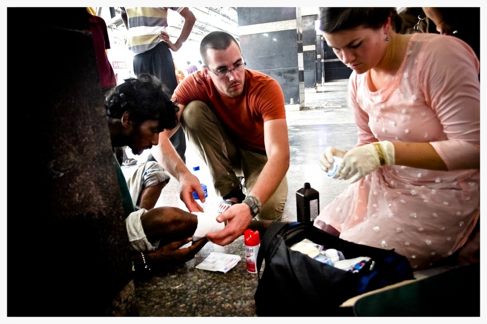 Grant Dailey assists Rebekah Davis in mending a wound on an injured elderly man in India. Basic wound care is life-saving in third world environments without proper sanitation, access to water and basic medical supplies.