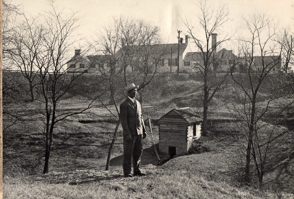 "Jim Winters, born 1887, was one of Hopewell's first residents.  Pictured in 1947, he is standing in front of the former Bondurant estate. Jim remembers his mother, who worked as a dairy servant for the Bondurant family, ""made many a trip down the hill from the big house to bring up cold milk and firm golden butter from the springhouse."""
