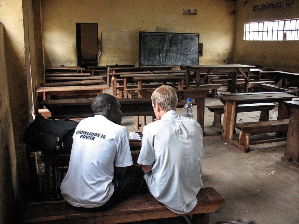 "Rylan Aaseby (right) and a Ugandan high schooler study the bible after his classes at Kakungulu Secondary School in Bombo in 2006. Though little phrases like ""knowledge is power"" litter the Ugandan school system, very few receive the kind of education that is empowering."