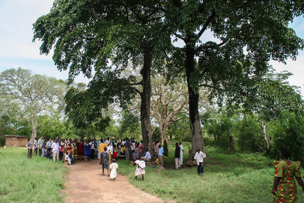 In rural Uganda, many churches and schools meet under the shade of trees because they lack a building sufficient for the number of people that congregate. The presence of God is no less present in this humble abode. Dozens gather beneath the shady tree for songs, testimonies, and a bible study during a bible conference.