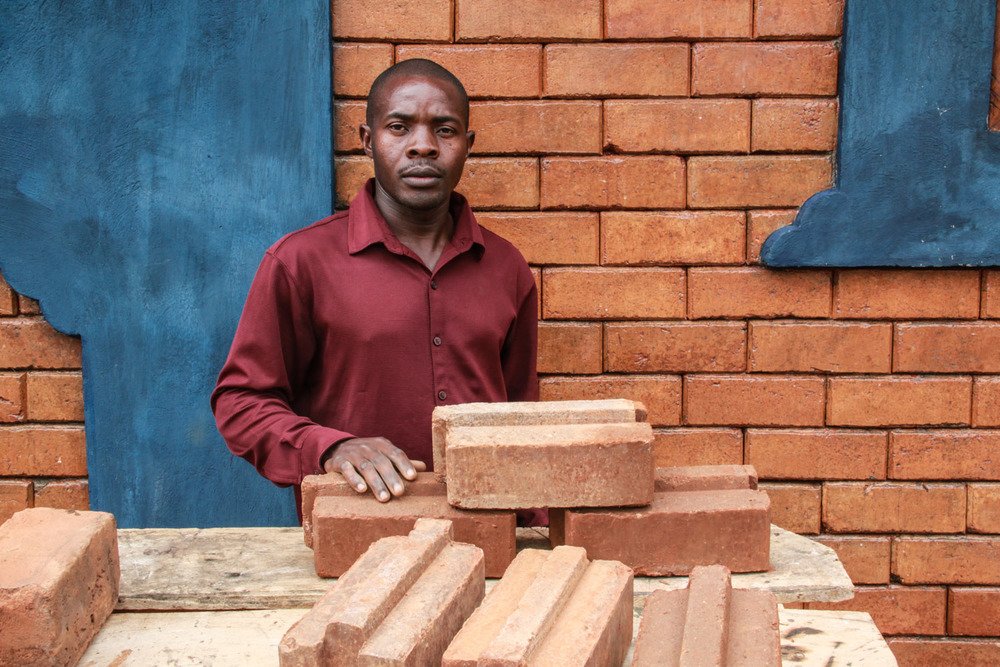Francis Lubega, G.O.D. Int'l East African cooperative, explains the process of making Interlocking Stablized Soil Block bricks. ISSB bricks are more economical and ecological than local mud bricks that require burning and often crumble. Lubega is trained to build with ISSB as he thinks it can benefit many people in his community.