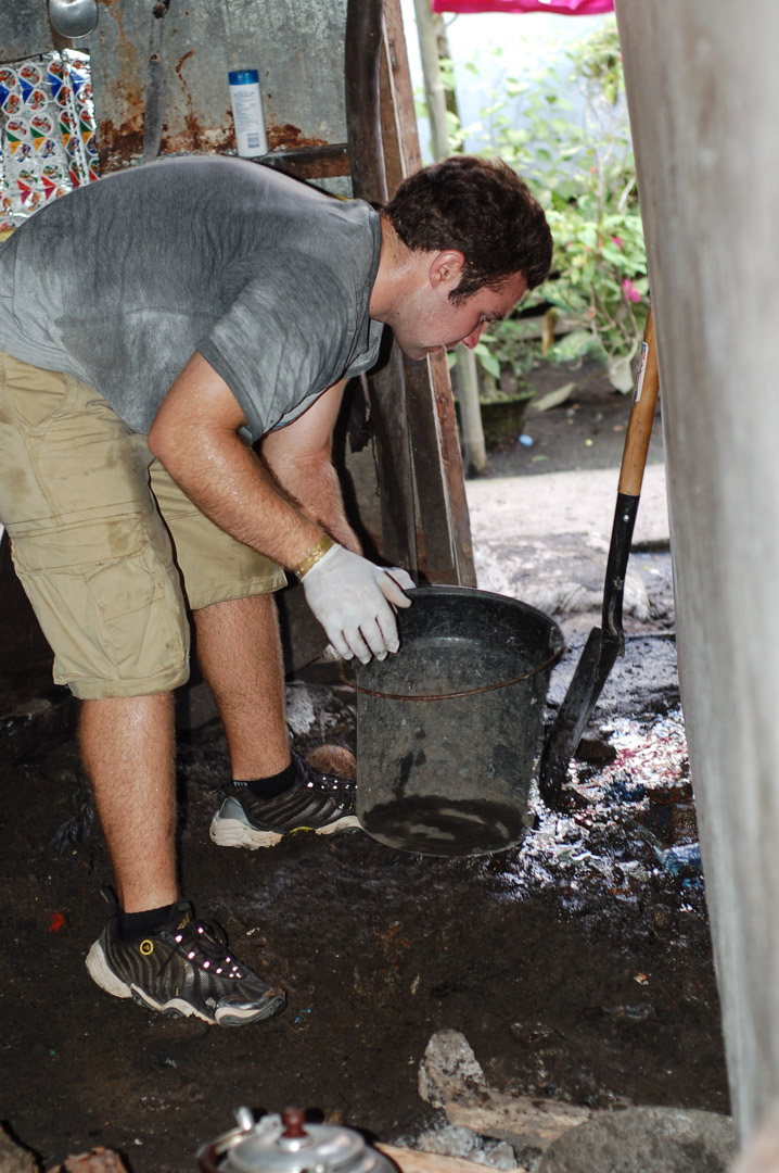 Craig Duffy assists in the cleanup of a house in Sagkahan in 2006.  The lack of access to basic utilities leads to unsanitary living conditions in houses such as this.  The bucket in his hand is one of several that contained human feces that were removed to help sanitize the house.