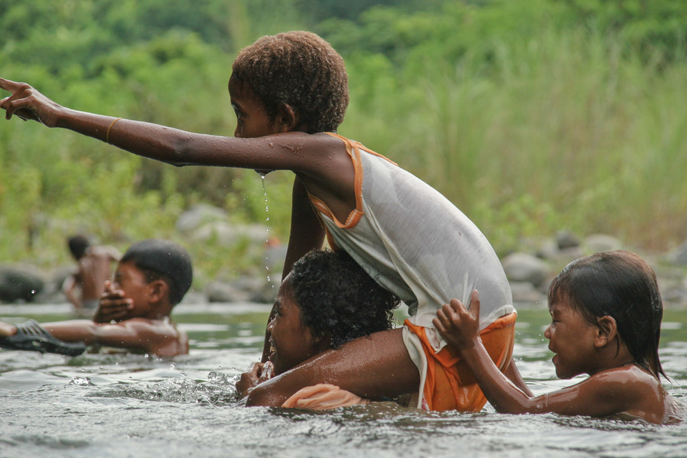 A group of indigenous children from an Aeta tribe enjoy a hot day's swim in the mountain river.  The river is a source of drinking water, cooking water, bathing, food (crabs and fish), and clothes washing for this tribe that is largely disconnected from the technologies of the surrounding society.
