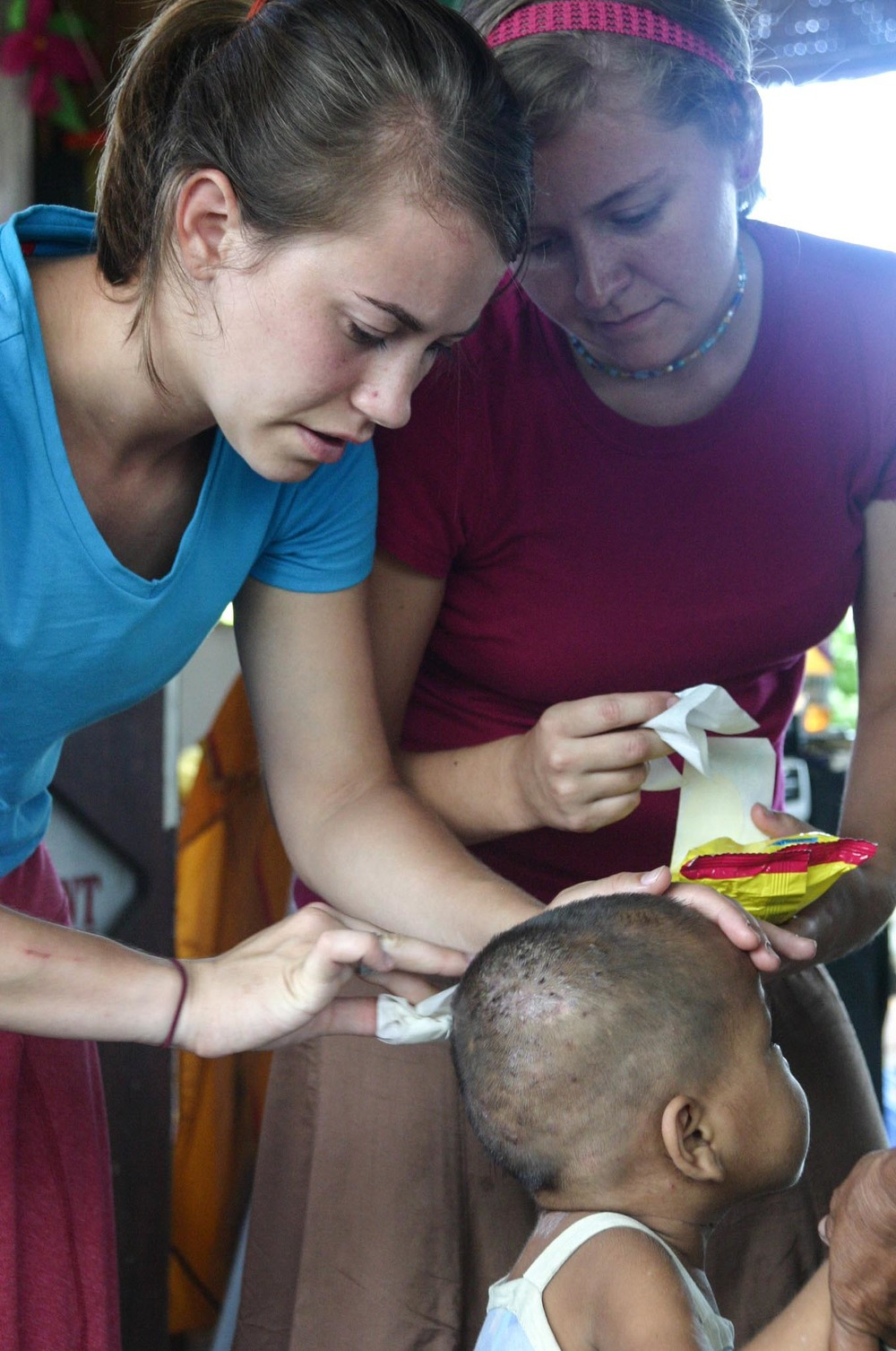 Kathryn Montgomery and Cannon Cameron perform basic wound care on a child living in a squatter village.  Minor cuts and wounds can become major infections in only a few days if not treated properly, which is sadly the case for many children who call these inhumane environments 'home'.