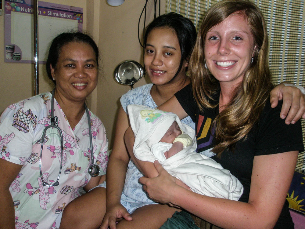 Meg Mathews assists in the labor and birth of the woman to her right alongside a local Filipina midwife.  In a nation where only 16% of women breastfeed exclusively, Meg is trained to offer not only childbirth education but also lactation consultation for new mothers.