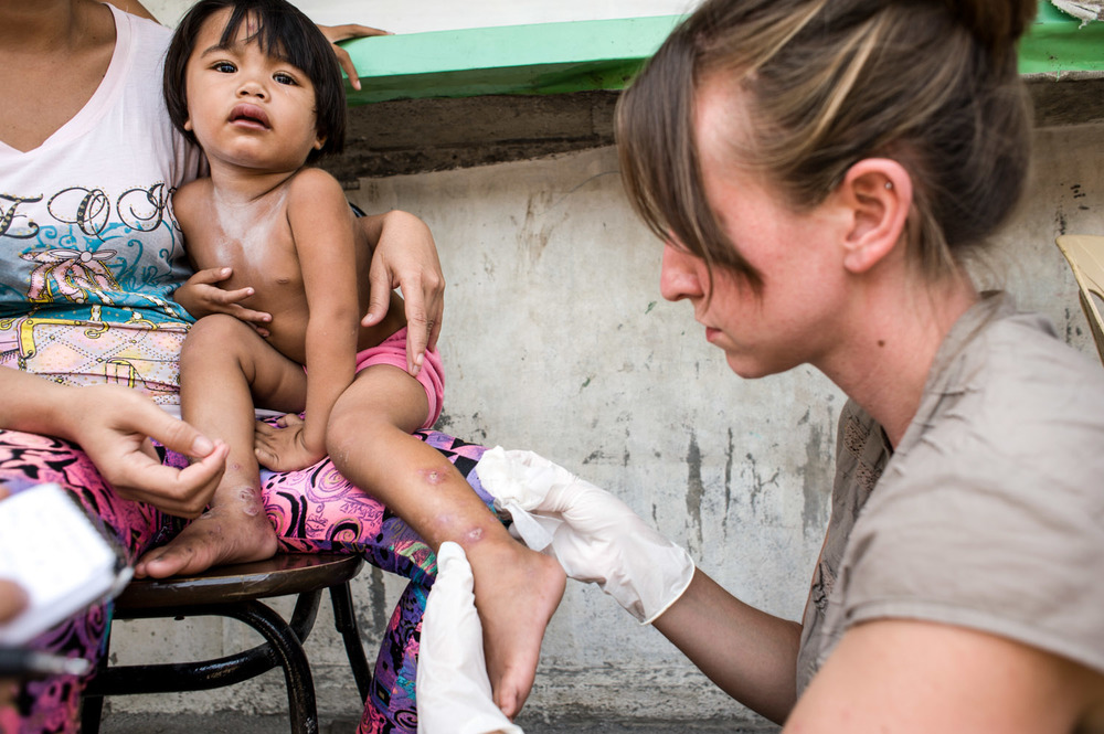 Access to healthcare for those who live in poverty is bleak.  Where the environment breeds poor sanitation, those who inhabit it are subject to disease and illness.  Sarah Mascaro, takes time to offer wound care to a child in a city slum - a service that is simple, yet so lacking these environments.
