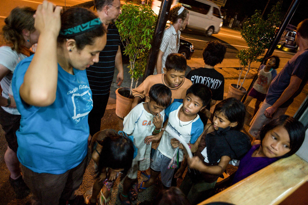 Leafa Vagatai and other team members talk with children on the streets in Barrio Barreto. This area is known for having a thriving 'sex tourism industry' that attracts men from different parts of the world who come to exploit young Filipina women. Many of the girls are brought here against their will, while others are drawn by the promise of an escape from poverty. The children that frequent the streets are extremely vulnerable to abuse by sexual predators, others that look take advantage of them.