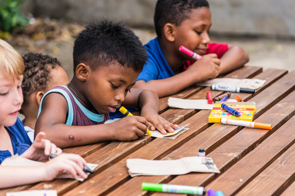 Elijah Galford (Left), the son of Shaun and Candace, colors alongside new friends, John Steven and William, at a weekly children's education program facilitated by the South East Asia Team during the Summer of 2013.