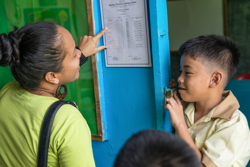 Rina Miller is a G.O.D. South East Asia cooperative.  She is a trained social worker that focuses on social reintegration of marginalized peoples. In this picture she is getting to know a child outside his classroom at an elementary school in Cebu.