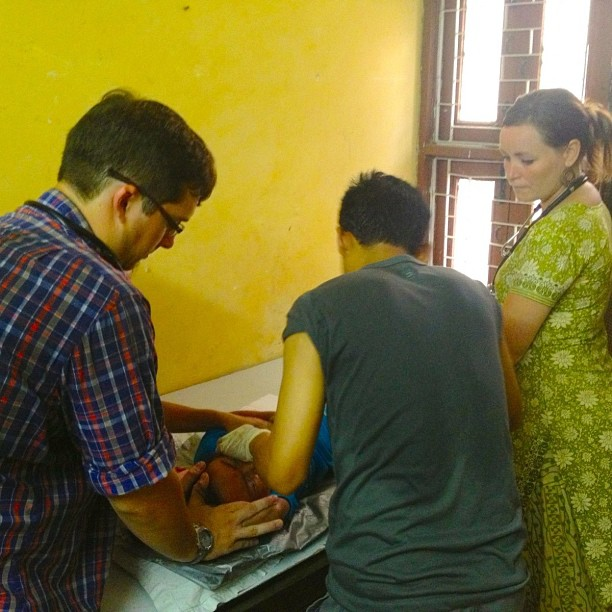 Nick Moore and Jenny Ebert assist in a draining of an abscessed chin in a local clinic. Abscesses are common because of the lack of sanitation available to many children.