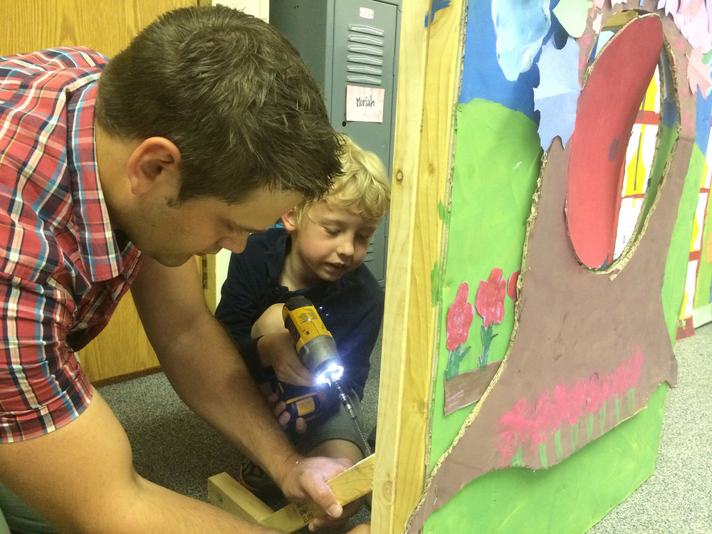 Mr. Olson works with Asher to help construct supports for the school-wide puppet show. The students built the entire set, and loved learning to use the drill to do it!