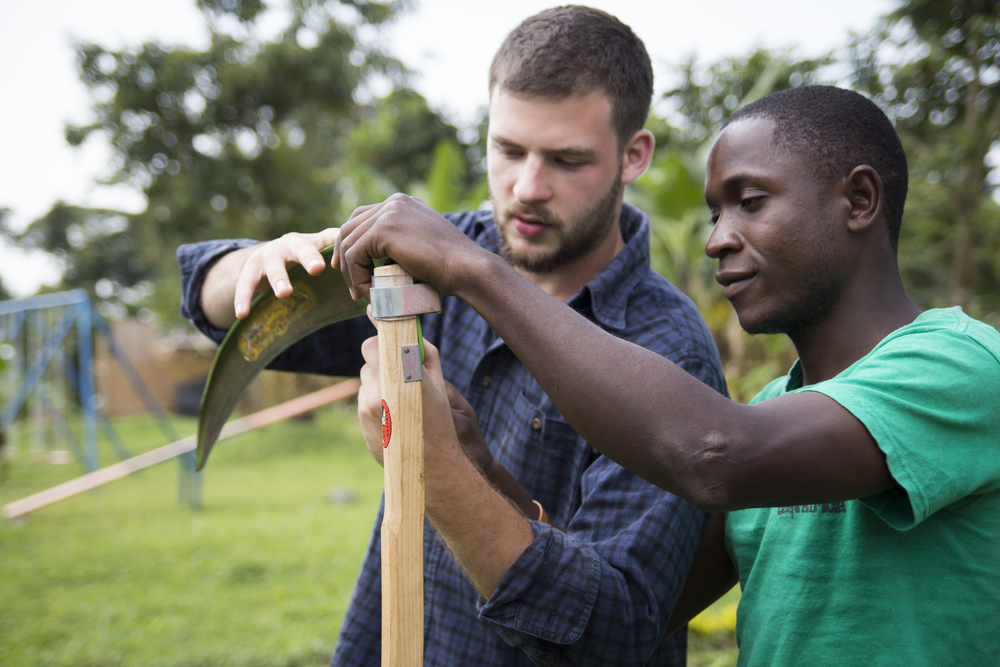AJ Gerard trains Andrew, of Uganda, on how to properly care for the blade on the end of the scythe. Andrew has spent the last several months employed to slash grass on a large compound. He was extremely interested in the scythe, and encouraged by how much time it saved him in his work. With his extra hours, he can now contribute more time to food production in the community garden.