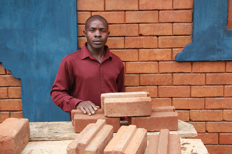 "Francis Lubega, G.O.D. Uganda cooperative, is our expert on Compressed Earth Block. This particular kind of brick is called an ""interlocking stabilized soil block,"" (ISSB). After a few months of building with ISSBs, Lubega would not go back to traditional brick laying. He says ""with ISSBs, one learns to work together. With the old bricks, you would do that by yourself. But with ISSBs, the work goes very fast, but you need a team to work together."""