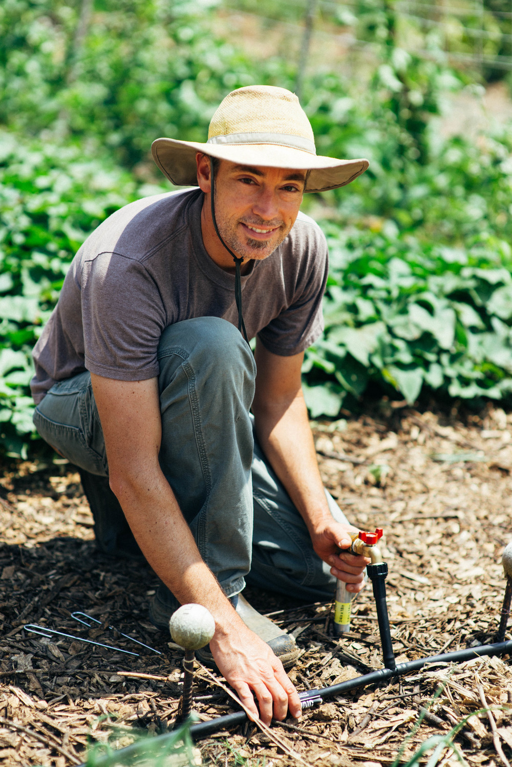 Seth Davis, Director of Hopewell Gardens, tests the newly installed irrigation system.   Lack of water conservation and storage in the developing world leaves farmers and their families susceptible to drought and famine during dry seasons. Simple, low-cost drip-irrigation systems like this one are believed to be a necessary innovation.
