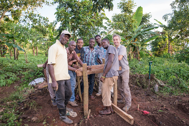 The men pose proudly near their newly constructed stand, ready to position the water tank for the drip irrigation system.