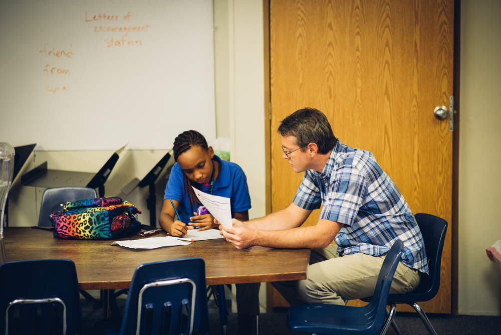 Shaun Galford, a teacher at both G.O.D. Elementary and the Institute for G.O.D. Int'l, assists Alicia with her homework. CASE provides students with one-on-one tutoring, a service that has produced noticeable improvements in students' academic performance and enthusiasm for learning.