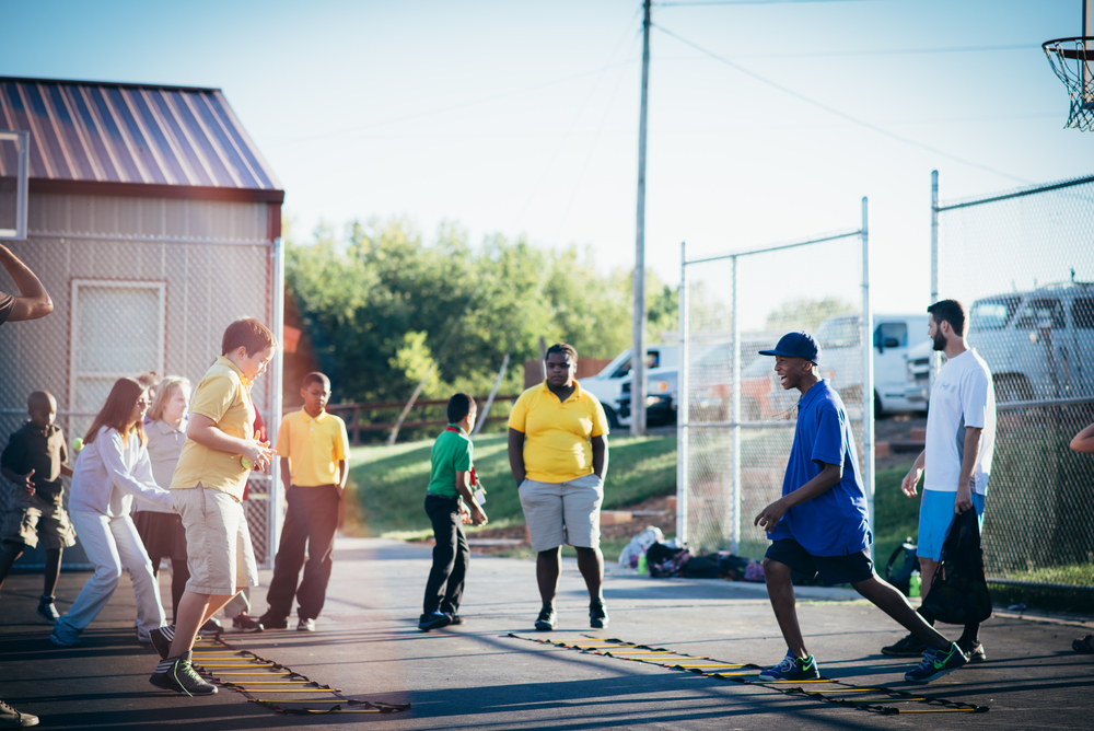 Derek Bargatze, Physical Education teacher at G.O.D. Elementary, observes students as they develop their footwork using the agility ladder during a coordination and balance workshop.