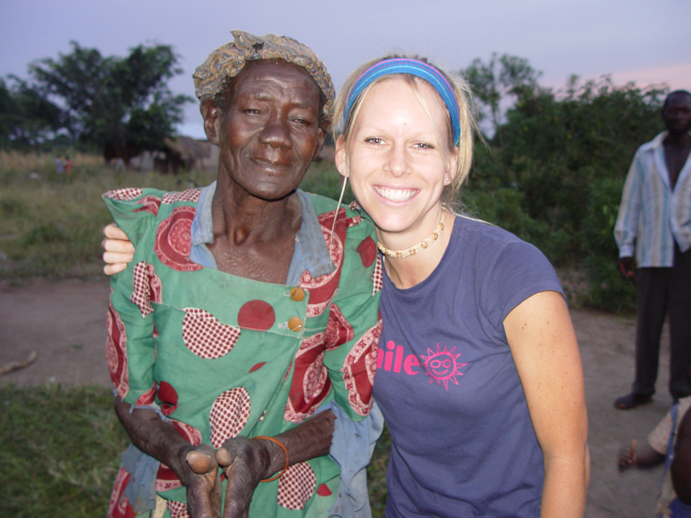 Tara Garner embraces an elderly woman from Uganda, after teaching women's health seminars (2005).