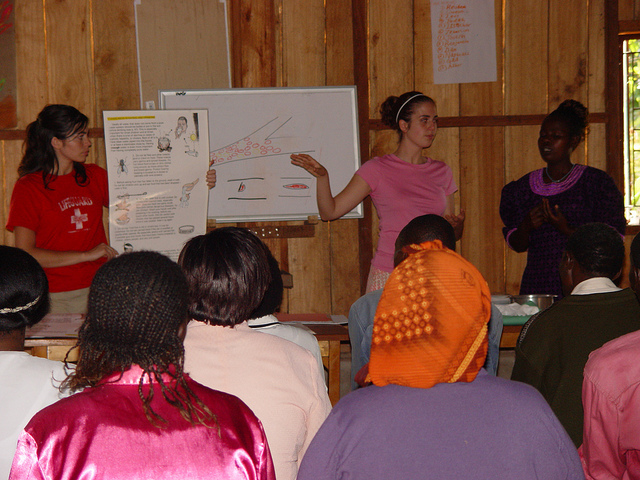 Heather Munoz (left) and Celesta Bargatze (right) teach a room full of Kenyan women about the importance of nutrition, and what preventative measures they can take to protect their households from diseases like malaria (2005).