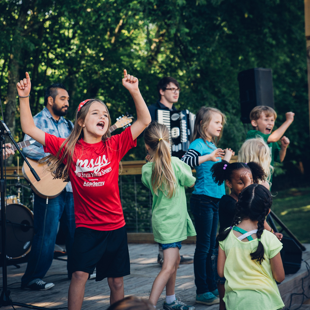 "Students celebrate on the last day of school during a worship time, thanking God for their year together. At the end, one young boy jumped on the stage and yelled ""I love this school!"""