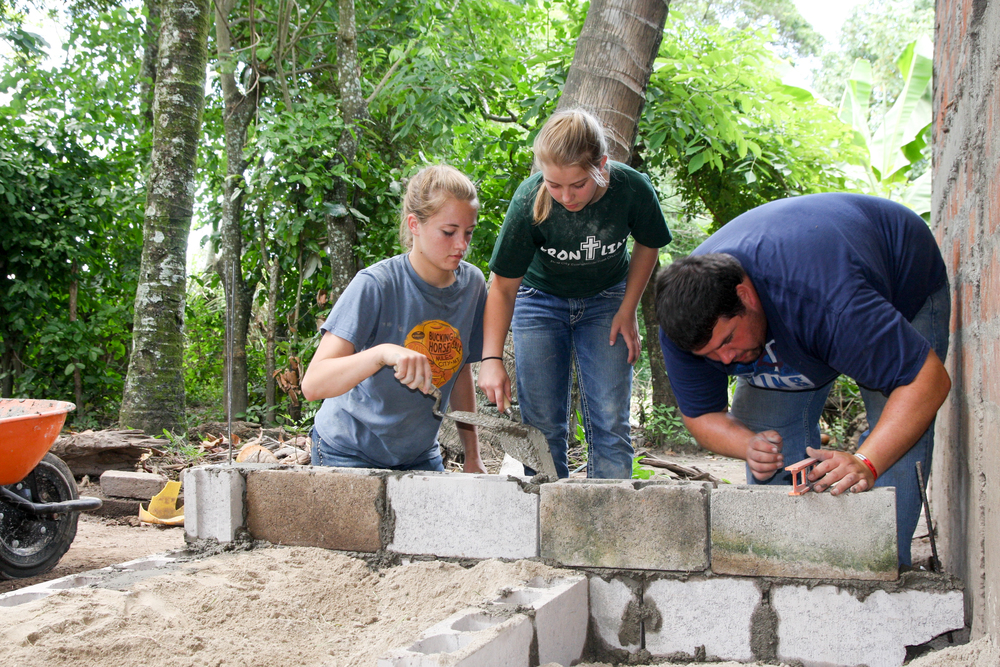 Shania, Kayla, and Savannah sift sand in order to make cement for the foundation of the smokeless kitchen.