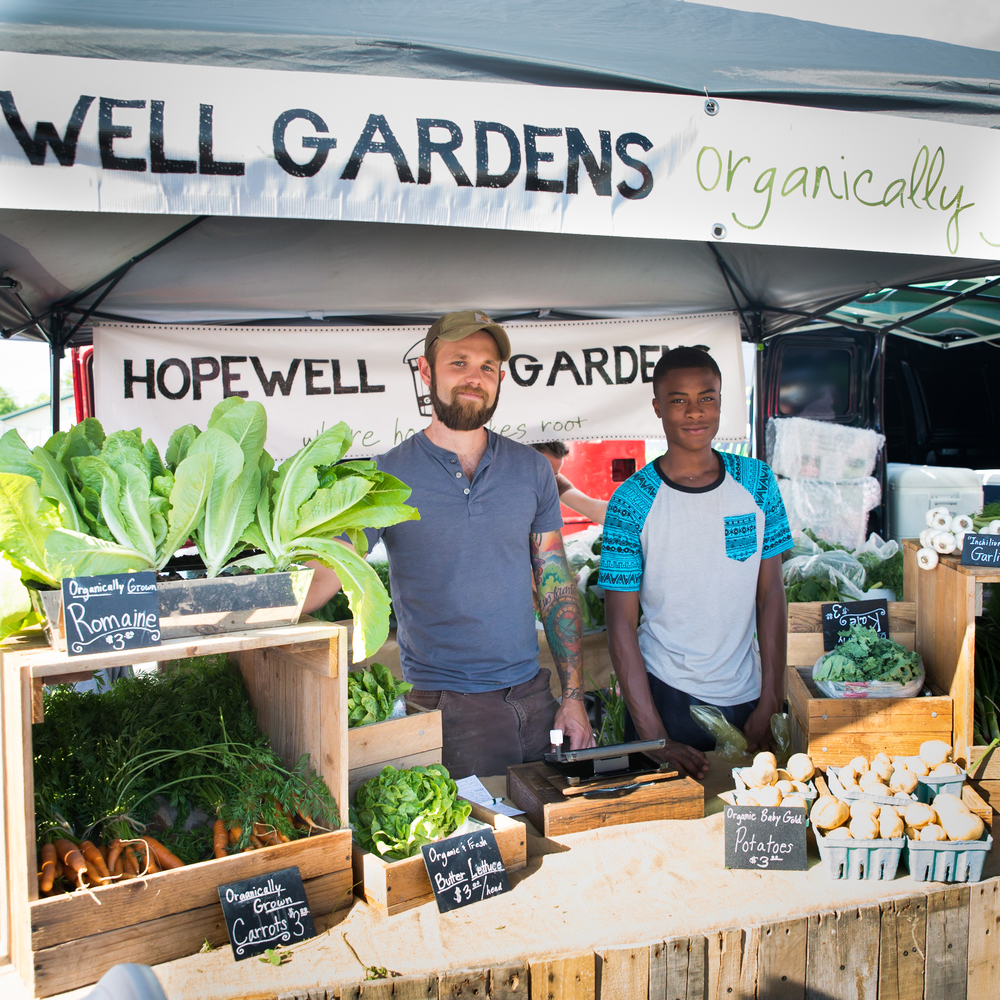 Geoff Hartnell is assisted by Gerron, a friend and neighbor, at the local farmer's market. Gerron was inspired after learning gardening at Camp Skillz, and created his own garden for his family in his backyard.