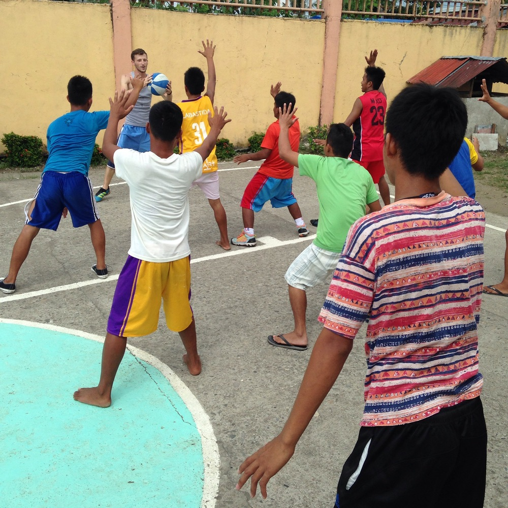 Clark works at a center for youth in conflict with the law twice a week.  Here, he facilitates a basketball camp completely in the language of the young men.