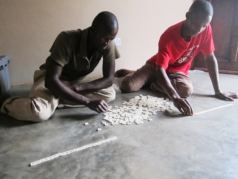 "Tom (l) and Simon Peter (r) work with ""banana gram"" letters to order the alphabet and begin forming their first English words."