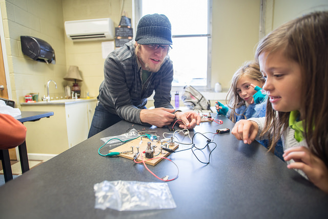 In Exploratory Hour, there's no limit to the challenges students undertake. Here, Academy teacher Skylar Aaseby has kids building light circuits in both series and parallel configurations with batteries and switches.