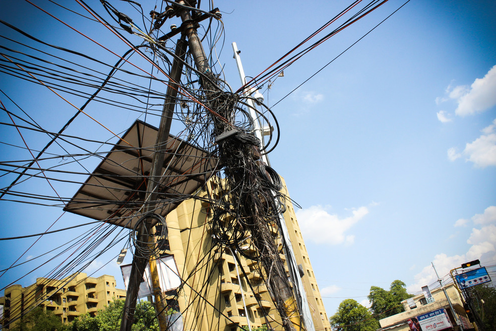 This web of electrical wires poses danger to the surrounding village, but is a common sight in India.