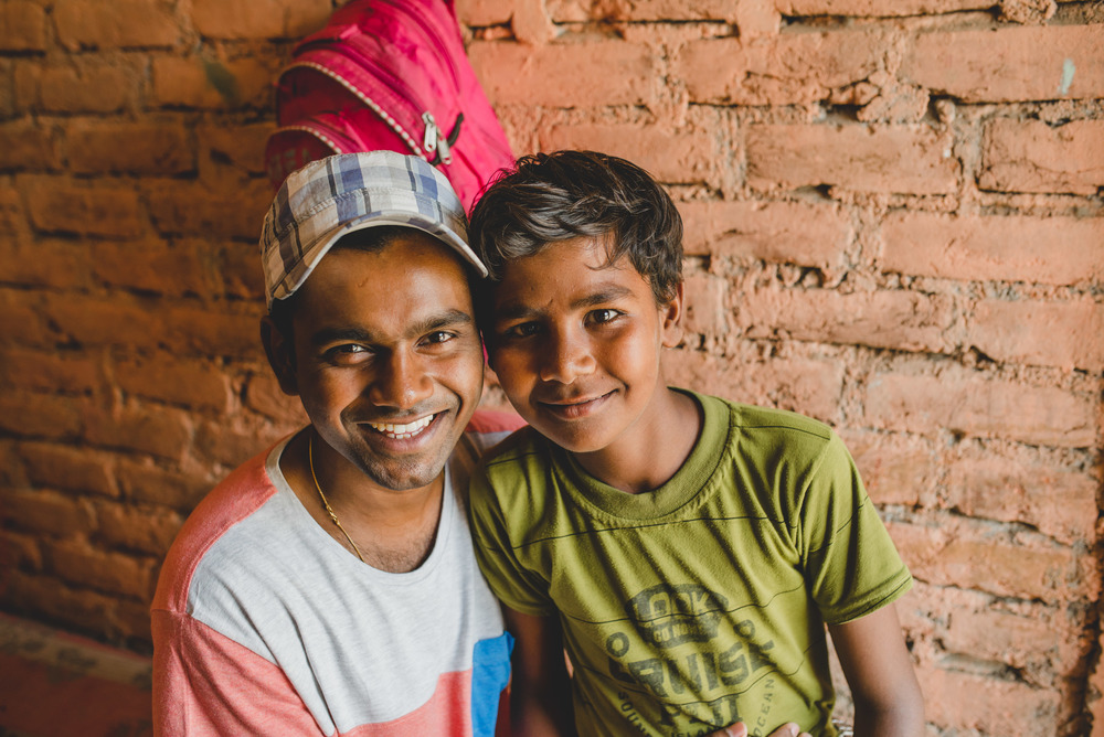 "As we visited with this little boy's mother, Manohar took time to show attention to him. He reminded him of his own childhood. ""I know what this family is going through because my family lived like this."""