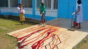 The blood-drenched clinic porch being cleaned off after pregnant, Cameroon mother dies along with her twin babies, for being refused treatment.