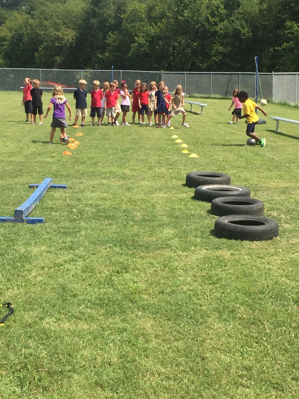 Students work their way through an obstacle course relay race in Coordination and Balance as their classmates cheer them on and watch to see who wins.