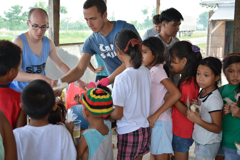 Participants on summer internship 2015 handout a snack during a kid's camp in Tacloban City, Leyte.  The camp was hosted at transitional housing for families who lost everything in Typhoon Haiyan in November of 2013.