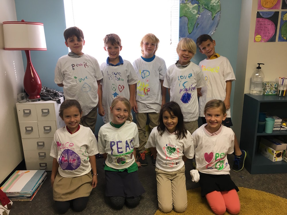 """Students took a moment to pose with their newly painted t-shirts filled with messages of peace. (Learn more about this project by reading the caption under the picture titled, """"Leymah Gbowee"""" in the pictures below.)"""