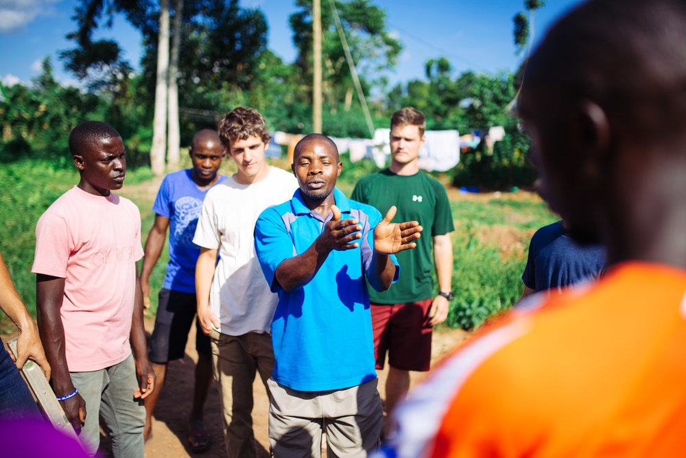 Francis Lubega instructs a small team on how to build rocket stoves and their benefit in homes in rural Uganda.