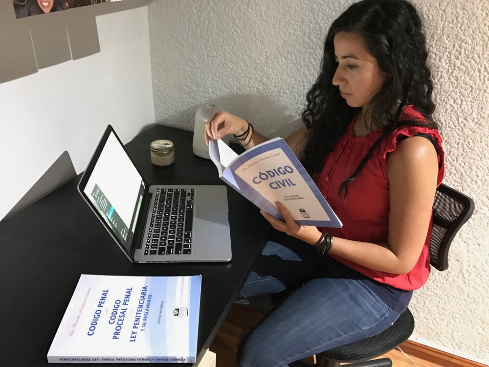 Team member Lavy Fernandez reviews necessary legal documents that advise us in operating as a NGO in El Salvador.