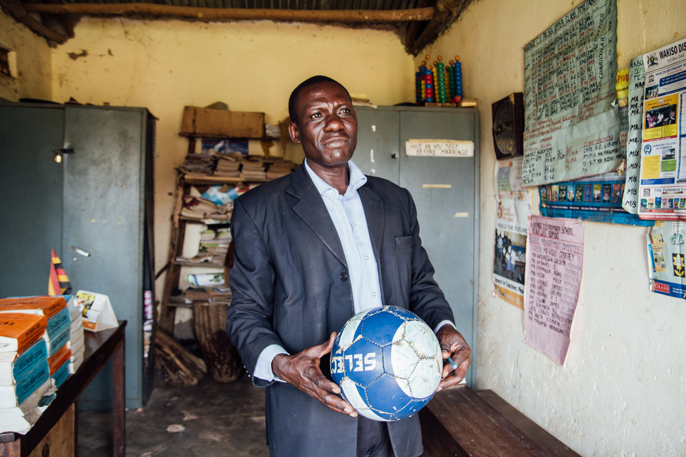 HM Stephen Kawuta in his office at St. John's Primary, holding one of the first footballs ever gifted to the school.