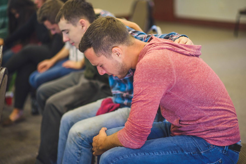 A group of students take a moment to pray for one another during a time of worship.  Times like this, remind us that this relational aspect of our faith is a necessary part of staying spiritually healthy.