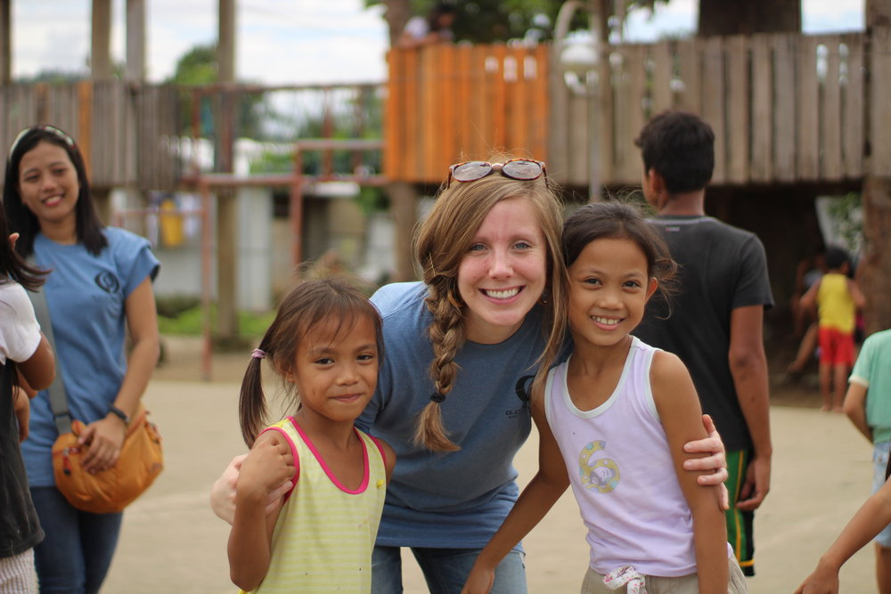The interns collaborated to put on 4 different kid camps for children in different barangays.  Team facilitator Meg Mathews takes a moment with two of the camp's participants.