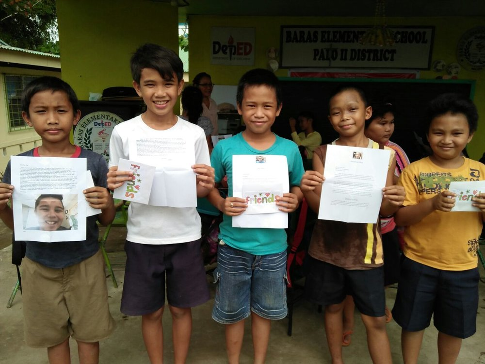 Students from Baras Elementary hold up their letters from our class!